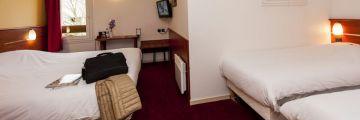 Une chambre avec 3 lits à Agen